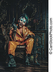 evil clown man - Evil clown man stained in blood is sitting...