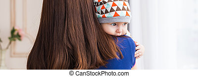 Adorable Caucasian baby with his mother. Portrait of a three...
