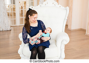 Portrait of a cute baby boy with his mother. Adorable three...