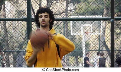 Young man play basketball ball turn on finger streetball...