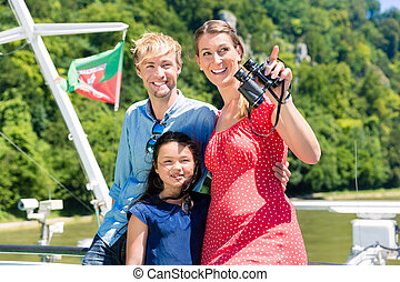 Family on river cruise with binoculars in summer enjoying...