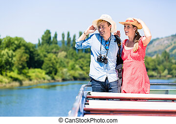 Happy couple on river cruise wearing sun hats in summer...