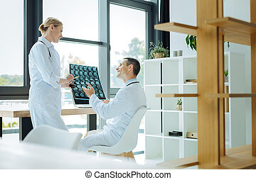 Joyful positive doctors talking to each other - Professional...