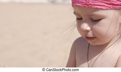 Little cute girl playing with sand and seashells on the beach. Close up in UHD