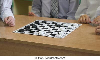 The children play checkers in kindergarten indoors -...