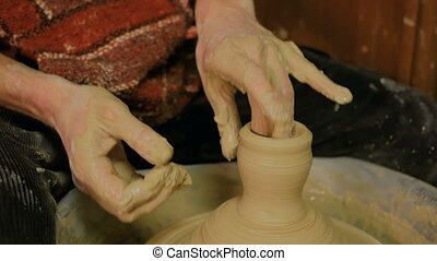 Professional male potter making mug in pottery workshop,...