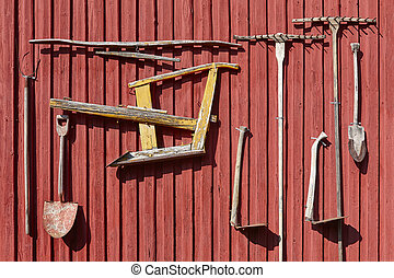 Farm old equipment hanging on a red wall. Agriculture