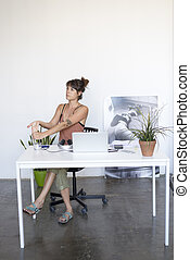 Businesswoman sitting at the table in office and stretching