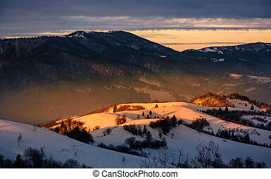 winter sunrise in mountainous rural area - beautiful warm...