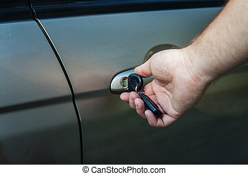 man's hand opens the car door with a key
