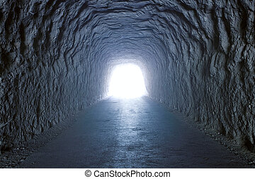 Inside a tunnel inside a mountain with light at the end