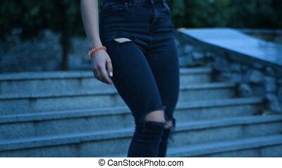 girl in a black t-shirt and jeans descends the stairs on the...