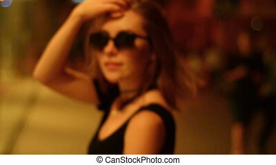 attractive lady in glasses goes at night on the street looks...