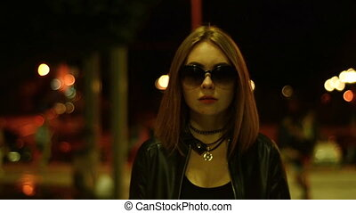 pretty serious Lady in glasses goes city at night looks into...