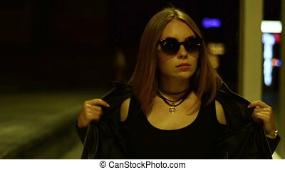 charming girl in black glasses goes night street leather...
