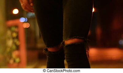 girl walking down the street wearing jeans with holes - a...