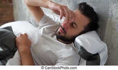 Sick millennial guy lying in bed and sneezing - Having no...