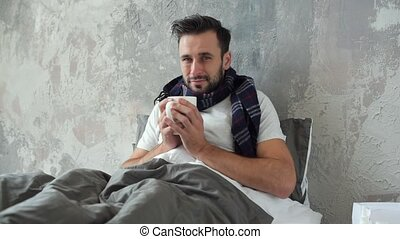 Poor young man drinking warm tea while feeling ill - Staying...