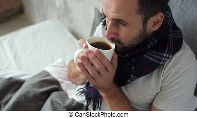 Close up of ill man drinking tea in bed - Feeling much...