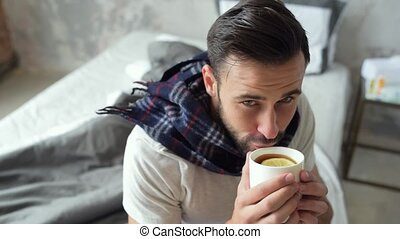 Bearded millennial guy drinking tea and smiling into camera...