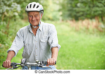 Senior Man Enjoying Cycle Ride In The Countryside