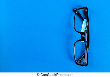Modern fashionable and office spectacles on blue background, Perfect reflection, eye glasses on table for copy space