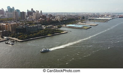 Aerial view of the boat riding through East river near shore...