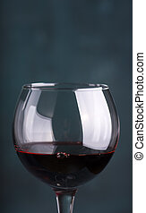 Pouring red wine into the glass against wooden background.