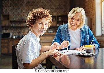 Excited curly haired child enjoying spending time with...