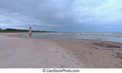 Woman with towel walking along the sea