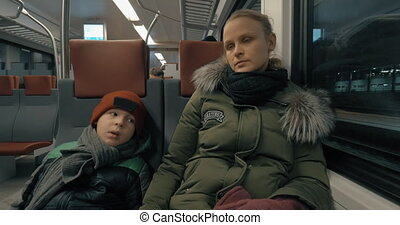 Mother and child having a ride in suburban train - Mother...