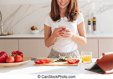 Cropped image of a pretty smiling woman using mobile phone...