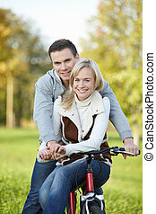 Happiness - Attractive young couple on a bicycle in the park