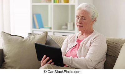 senior woman with tablet pc and credit card - technology,...
