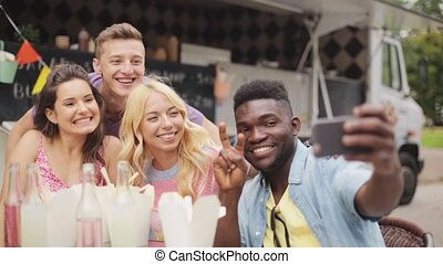 happy young friends taking selfie at food truck - leisure...