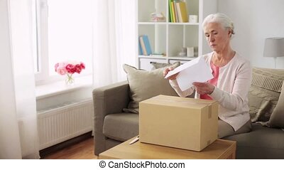 happy senior woman opening parcel box at home