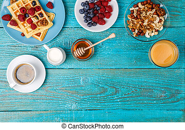 Homemade waffles, fresh raspberries and blueberry, cup of...