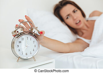 Close up of a woman turning off alarm clock in the morning...