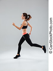 Full length picture of a sports woman running in studio over...