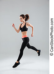 Full length image of a sports woman running in studio over...