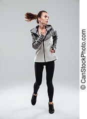 Full length picture of a attractive female runner running in...