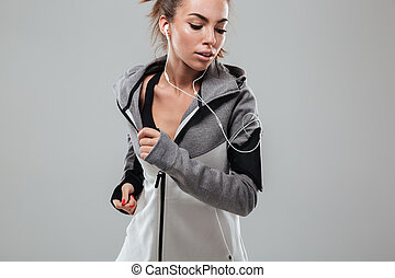 Young female runner in warm clothes running in studio and...
