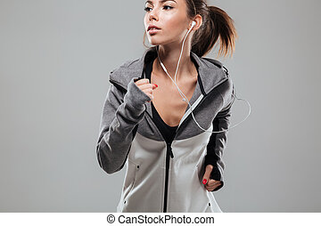 Pretty female runner in warm clothes running in studio and...