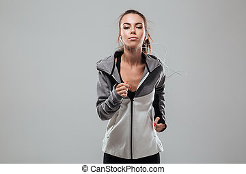 Serious female runner in warm clothes running in studio and...