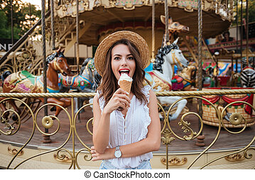 Happy pretty girl eating ice cream while standing in front...