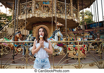 Young beautiful girl eating ice cream while standing in...