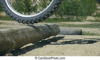 Motocross rider overcomes barrier from wooden log. Enduro...