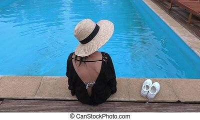 Woman in straw hat at the pool