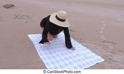 Woman sits on the beach towel