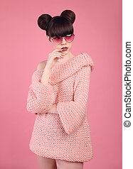 Pretty teen girl in knitted sweater over pink background....